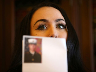Former United States Marine Erika Butner holds up picture