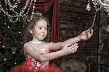 Little girl in red princess dress and chandelier with crystal