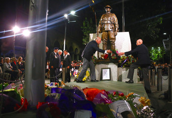 Veterans move wreaths and floral tributes after they had been laid around the Cenotaph during the annual ANZAC Day dawn service in Sydney, Australia