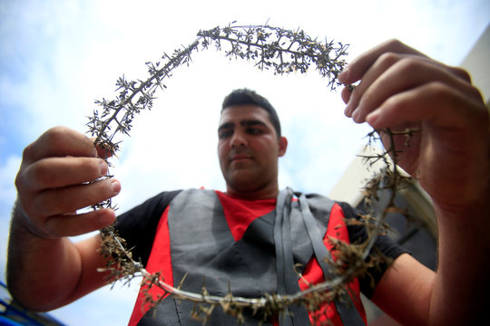 A Christian man carries a crown of thorns during a re-enactment of the crucifixion of Jesus Christ on Good Friday in al-Qraya village