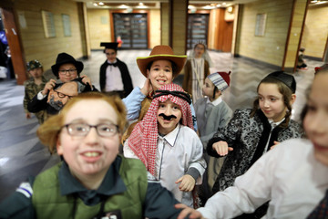 Children dressed up in Purim costumes play outside a synagogue, as others take part in the reading from the Book of Esther ceremony performed on the Jewish holiday of Purim, in Jerusalem