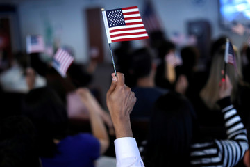 New American citizens wave American flags after taking the Oath of Allegiance during a naturalization ceremony in Newark