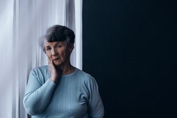 Elderly woman standing beside window Wall mural