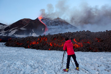 A tourist stands in front of Italy's Mount Etna, Europe's tallest and most active volcano, as it spews lava during an eruption on the southern island of Sicily