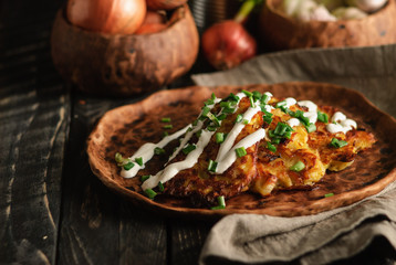 Traditional Belarus potato pancakes (draniki) with green onion and sour cream on a clay plate on a black wooden table.Close up, selective focus, copy space