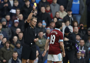 Burnley's Joey Barton is shown a yellow card by referee Graham Scott