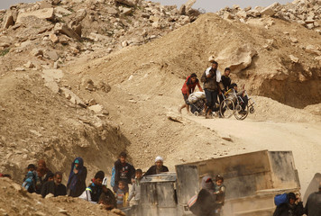 Displaced Iraqis flee their home while Iraqi forces battle with Islamic State militants, in western Mosul,