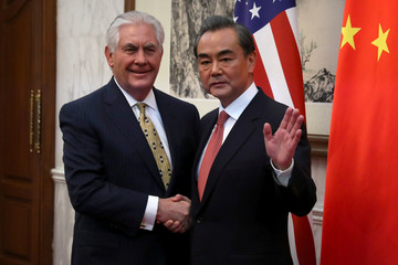 Chinese Foreign Minister Wang Yi gestures while shaking hands with U.S. Secretary of State Rex Tillerson before a bilateral meeting at the Diaoyutai State Guesthouse in Beijing