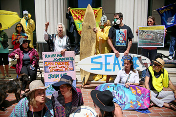 Protesters, some wearing wearing hazmat suits, stand outside San Diego Superior Courthouse to rally against nuclear waste disposal from the San Onofre Power Plant in San Diego