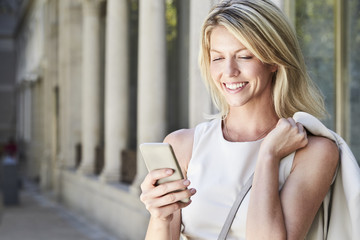 Beautiful woman texting on Smartphone, smiling