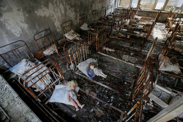 Dolls, which were placed by a visitor, lie at beds at a kindergarten in the abandoned city of Pripyat near the Chernobyl nuclear power plant in Ukraine