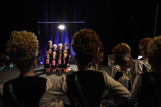 Dancers look on backstage as a performing group have their photo taken before performing during the World Irish Dancing Championships in Dublin