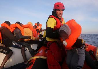 Rescuer helps migrants board a RHIB in central Mediterranean Sea