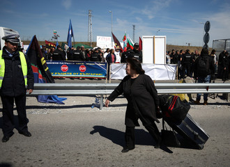 Woman carries her luggage as she crosses the border crossing between Turkey and Bulgaria on foot during a protest at Kapitan Andreevo border checkpoint