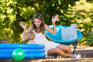 Mother bathes the baby in an inflatable pool in nature and plays with it in the ball