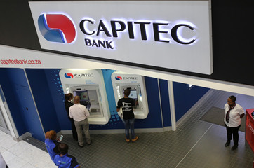 Customers queue to draw money from an ATM outside a branch of South Africa's Capitec Bank in Johannesburg,South Africa