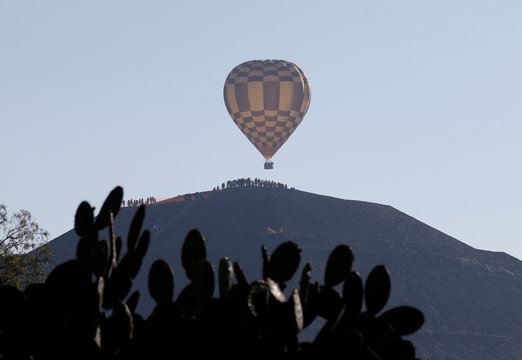 Hot air balloons float above people waiting to welcome the spring equinox while standing on the Pyramid of the Sun in the pre-hispanic city of Teotihuacan, on the outskirts of Mexico City