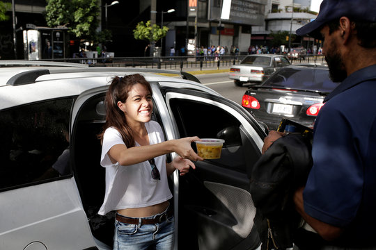Mariana Zuniga, volunteer of Make The Difference (Haz La Diferencia) charity initiative, gives a cup of soup to a man in a street of Caracas