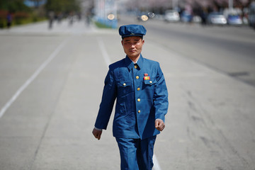 A man wears a pin with pictures of former North Korean leaders Kim Il sung and Kim Jong il in central Pyongyang