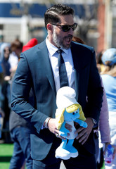"""Actor Joe Manganiello holds a Smurfette character as he arrives at the premiere of the film """"Smurfs: The Lost Village"""" in Culver City"""
