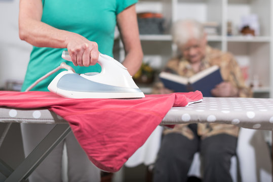 Home helper ironing clothes for an old woman