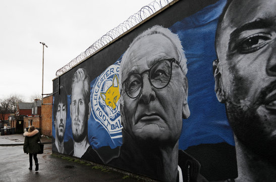 A girl walks past a mural of former Leicester City manager Claudio Ranieri ahead of the game