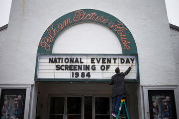 A man places letters on a sign board ahead of screening for the movie 1984 in Pelham, New York