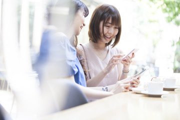 Two women are laughing at the smartphone