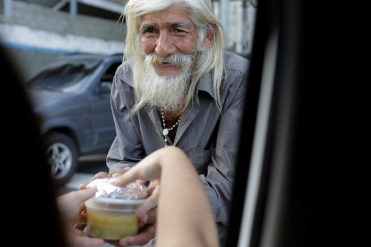 A volunteer of Make The Difference (Haz La Diferencia) charity initiative gives through a car's window a cup of soup to a homeless man in a street of Caracas