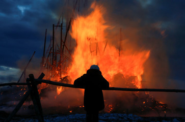 A woman looks at burning installation during the performance devoted to Maslenitsa in the village of Nikola-Lenivets.