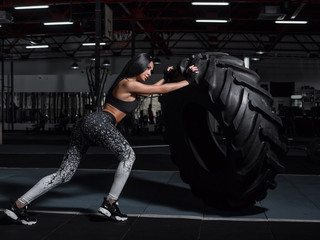 The athlete pushes a large wheel. Exercise with heavy weight in the gym.