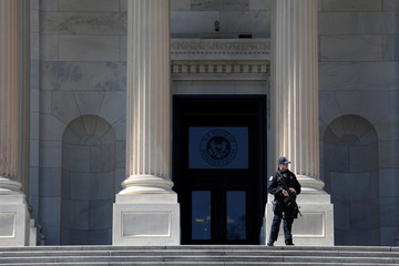 A member of the Capitol Police armed with a rifle stands guard outside the Capitol Building in Washington