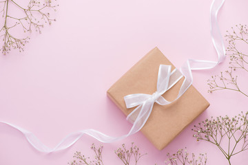 Kraft paper gift box tied with pink ribbon and white flowers for mothers day