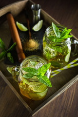 Mojito served on wooden tray with lime and mint