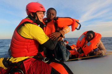 Spanish rescuer Daniel Calvelo, 26, carries a child into a RHIB during a search and rescue operation by Spanish NGO Proactiva Open Arms, in central Mediterranean Sea