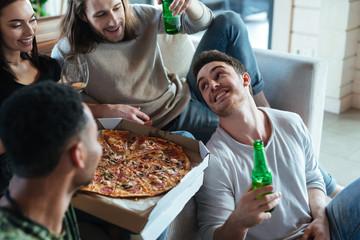 Cropped image of four friends sitting with pizza