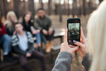 Friends sitting outdoors in the forest. Focus on phone.