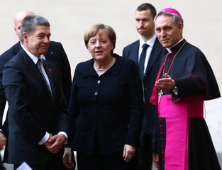Archbishop Ganswein greets German Chancellor Merkel and her husband Joachim Sauer as they arrive for a meeting with Pope Francis at the Vatican