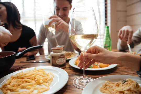 Closeup of people drinking wine and eating pasta at table