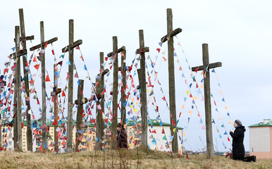 A woman prays on a hill near wooden crosses after a procession marking the Palm Sunday in the town of Ashmyany