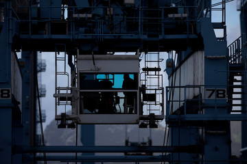A docker is silhouetted inside the cabin of a crane as he loads a container onto a truck in a cargo terminal at the port of Algeciras