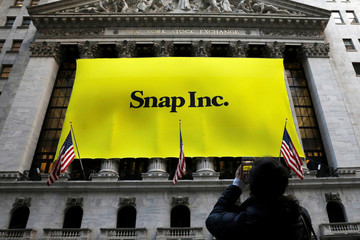 A woman photographs a banner for Snap Inc. on the facade of the New York Stock Exchange