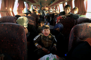 A boy who just fled a village controlled  by Islamic State fighters cries as he sits with his family inside a bus before heading to the camp at Hammam Ali  south of Mosul