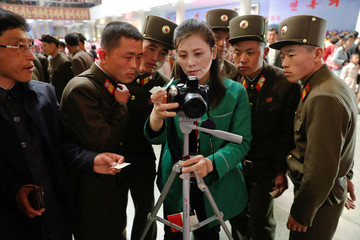 Soldiers check their souvenir photo as they visit the flower exhibition marking the 105th birth anniversary of the country's founding father, Kim Il Sung in Pyongyang