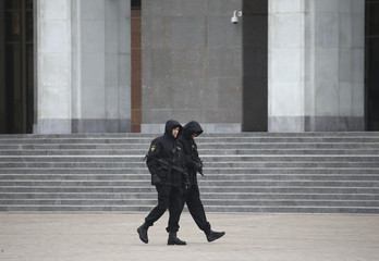 Armed police officers patrol Oktyabrskaya Square day before rally marking 99th anniversary of proclamation of Belarussian People's Republic in Minsk