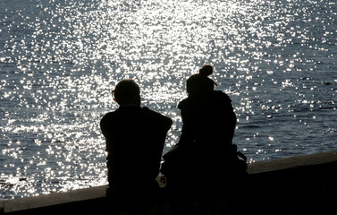 A couple is silhouetted at the harbour of Livorno