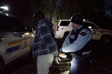 """A man who claimed to be from Sudan who kept saying """"I just want to be safe"""" is handcuffed by a Royal Canadian Mounted Police (RCMP) officer after he illegally crossed the U.S.-Canada border leading into Hemmingford"""