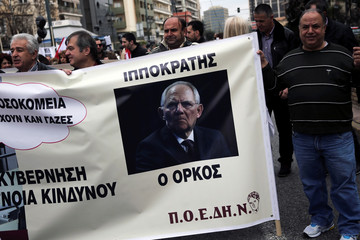 Public hospital doctors and health workers hold a banner with a photo of German Finance Minister Schaeuble during a demonstration over reforms to the social security system and the problems in the health sector after years of budget cuts in Athens