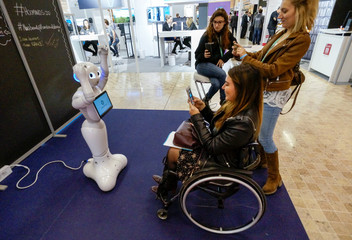 Visitors take pictures of SoftBank humanoid robot known as Pepper at the SIdO, the Connected Business trade show, in Lyon