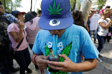 Teenager smokes marijuana out of a bong during a 4/20 party to demand legalization and to celebrate marijuana culture outside the Senate building in Mexico City